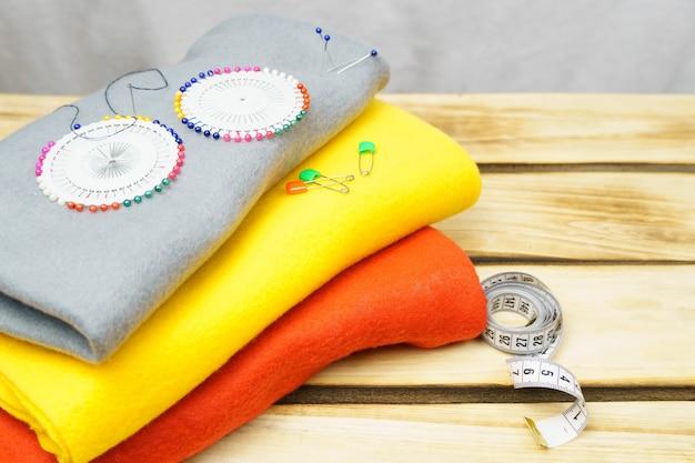 Разноцветные ткани и булавки на деревянном фоне.