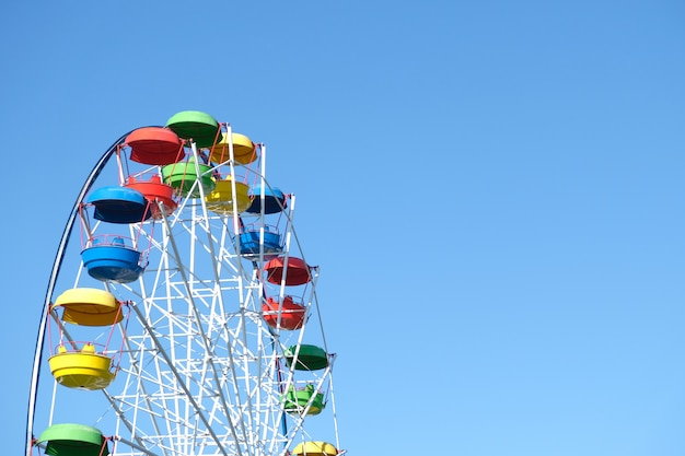 Multicolored ferris wheel against the blue sky.
