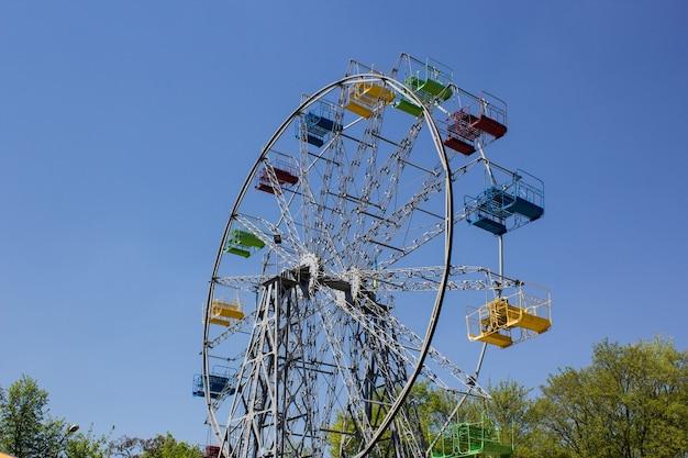 Разноцветное колесо обозрения с голубым небом в качестве фона