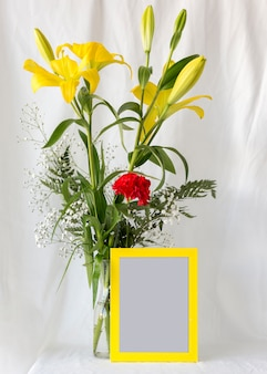 Multicolored flowers in flower vase with blank empty photo frame in front of white curtain