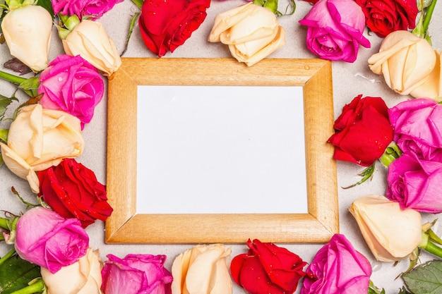 여러 가지 빛깔 된 신선한 장미와 가벼운 돌 배경에 나무 프레임. 축제 선물, 부활절, 생일, 발렌타인 데이 또는 결혼식을위한 인사말 카드. 휴일 개념, 텍스트를위한 장소