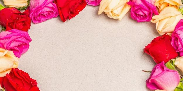가벼운 돌 배경에 프레임 모양에 여러 가지 빛깔 된 신선한 장미. 축제 선물, 부활절, 생일, 발렌타인 데이 또는 결혼식을위한 인사말 카드. 휴일 개념, 텍스트, 배너 장소