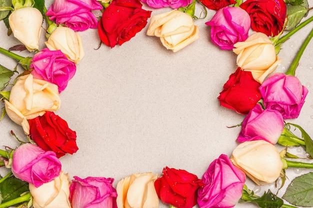가벼운 돌 배경에 프레임 모양에 여러 가지 빛깔 된 신선한 장미. 축제 선물, 부활절, 생일, 발렌타인 데이 또는 결혼식을위한 인사말 카드. 휴일 개념, 텍스트를위한 장소