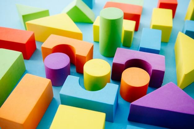 青色の背景に色とりどりの幾何学的図形。学習と