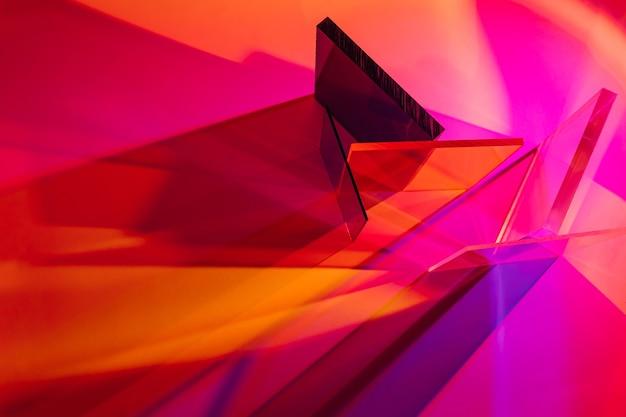 カラフルなグラデーションの背景に色とりどりのガラス。光はさまざまなアクリルシートを通過します。スタイリッシュな抽象的な背景