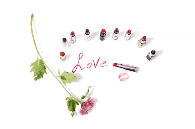 孤立した背景に色とりどりの光沢のある口紅。白い表面に野生の紫色の花。唇は紙にキスします。赤い唇の鉛筆の跡