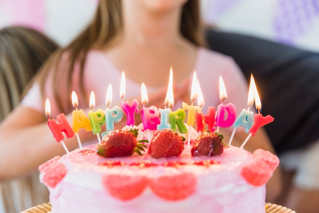 Multicolored glowing birthday candles on strawberry topping cake