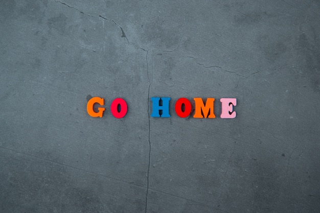 The multicolored go home word is made of wooden letters on a grey plastered wall.