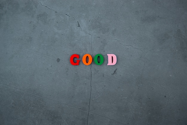 The multicolored good word is made of wooden letters on a grey plastered wall.