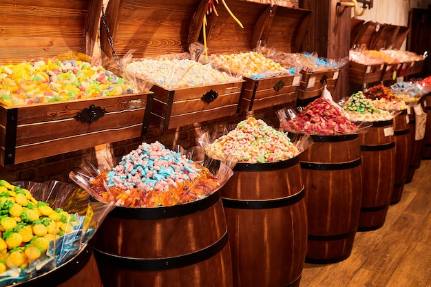 Разноцветные мармеладные конфеты и зефир продаются в магазине в деревянных бочках и сундуках.