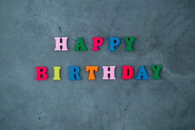 The multicolored happy birthday word is made of wooden letters on a grey plastered wall