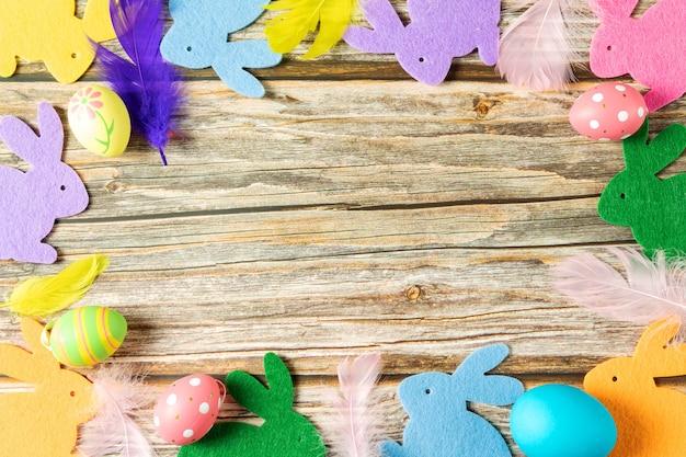 木製のテーブルの上の色とりどりのノウサギ、イースターノウサギ、上面図 Premium写真