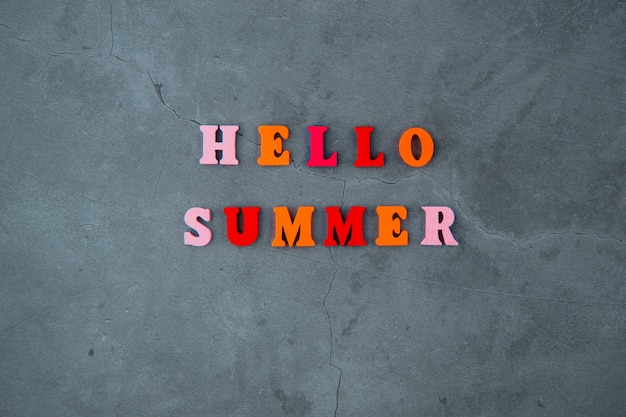 The multicolored hello summer word is made of wooden letters on a grey plastered wall.