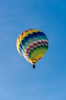 Multicolored hot air balloon seen from the ground