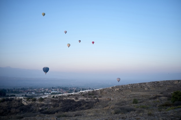 Multicolored hot air balloons flying in sunrise sky