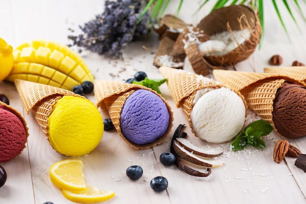Multicolored ice cream with berries and fruits on a wooden table