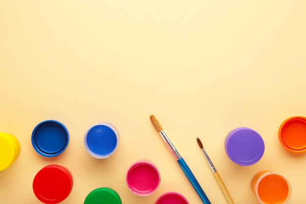 Multicolored jars of gouache and a brush on a beige background. creative kit.
