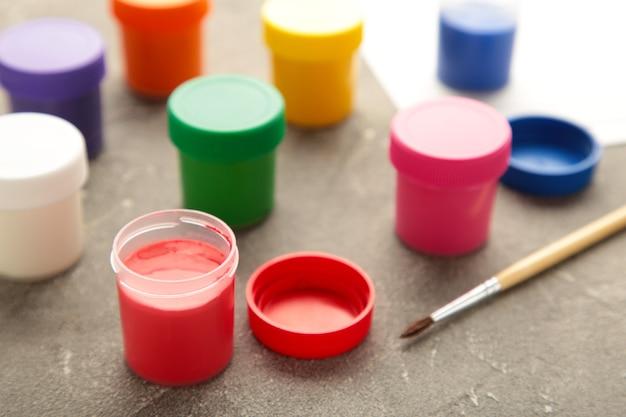 Разноцветные баночки с гуашью и кистью на сером столе. творческий комплект.