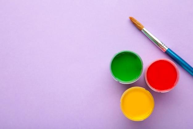 Разноцветные баночки с гуашью и кистью на фиолетовом фоне. творческий комплект.
