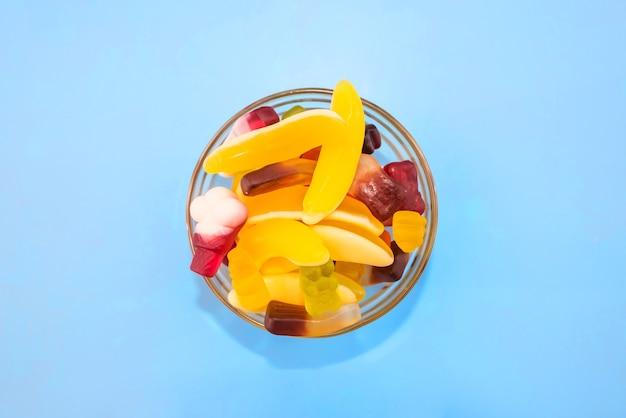 파란색 배경에 유리 접시에 여러 가지 빛깔의 젤리 사탕. 위에서 보기