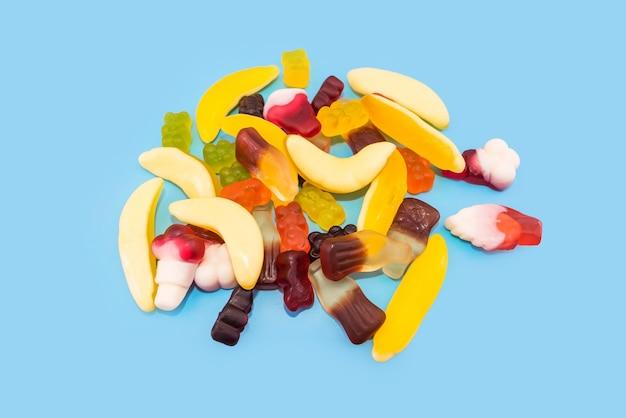 파란색 배경에 여러 가지 빛깔의 젤리 사탕