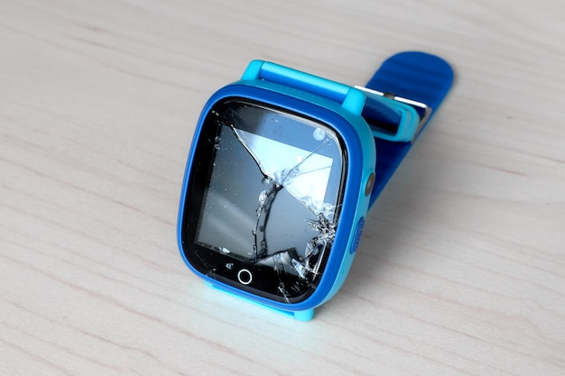 Multicolored kids smart watch phone with broken screen on a light wooden table. technology for children. wearable gadget concept. top view, close up. time clock for school.