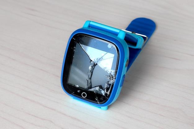 가벼운 나무 테이블에 깨진 스크린 여러 가지 빛깔 아이 스마트 시계 전화. 어린이를위한 기술. 웨어러블 가제트 개념. 상위 뷰를 닫습니다. 학교 시간 시계.