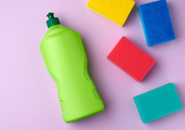 Multicolored kitchen rectangular dishwashing sponges and green plastic bottle with detergent