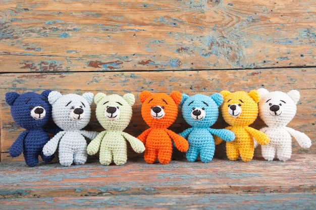 Multicolored knitted small bear on an old wooden background. handmade, knitted toy. amigurumi