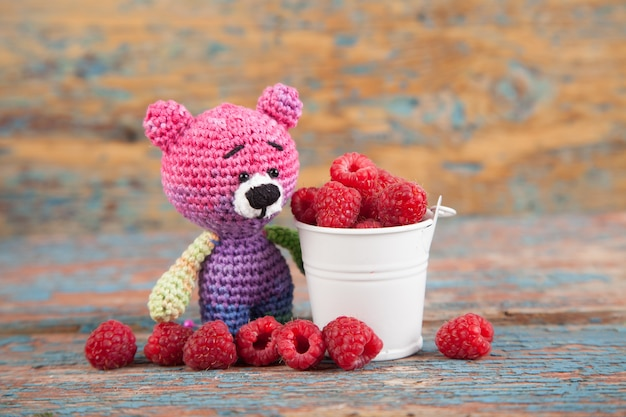 Multicolored knitted small bear with berry on an old wooden background. handmade, knitted toy. amigurumi