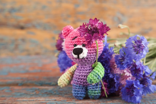 Multicolored knitted small bear with cornflowers on an old wooden background.
