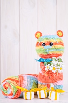 Multicolored knitted teddy with gifts and flowers.