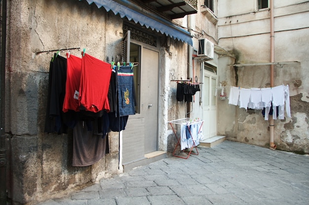 Multicolored laundered clothes are dried on the balcony in the alley of naples