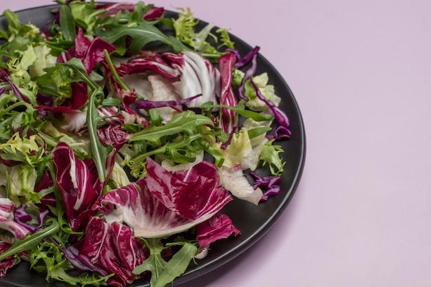 검정 잉크 판에 여러 가지 빛깔 된 잎이 많은 야채 믹스. 비건 음식. 깨끗한 식사. 공간 복사