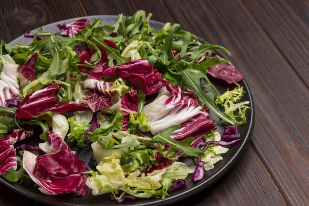 검정 잉크 판에 여러 가지 빛깔 된 잎이 많은 야채 믹스. 비건 음식. 면역 강화를위한 자연 요법. 평면도. 확대.