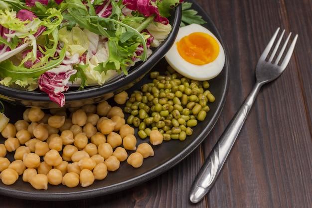 여러 가지 빛깔의 잎이 많은 채소, 병아리 콩, 녹두, 계란 및 포크를 검은 접시에 섞습니다. 균형 잡힌 영양.