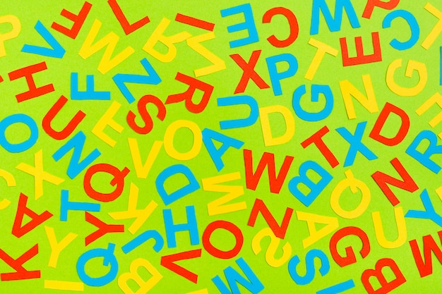 Multicolored letters of the english alphabet cut out of cardboard laid out randomly on a green background
