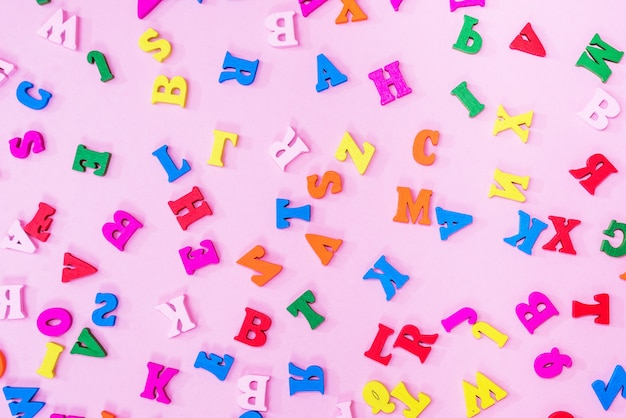 Multicolored letters of the english alphabet on a pink background, letters background. education concept.