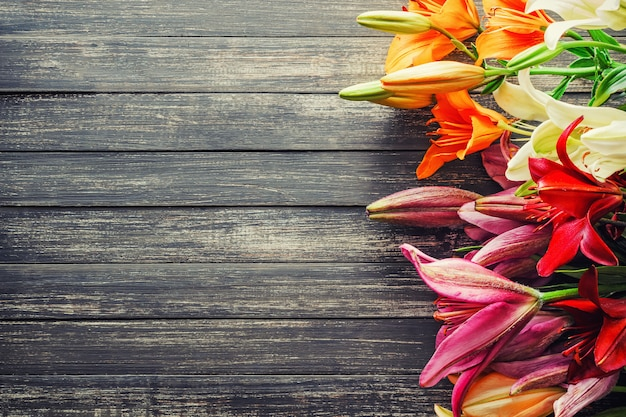 Multicolored lilies on old wooden board, background with copy space