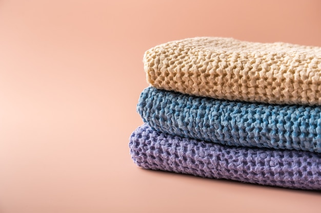 Multicolored linen and cotton bath and spa towels on pink