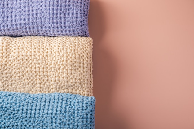 Multicolored linen and cotton bath and spa towels twisted into a roll on pink
