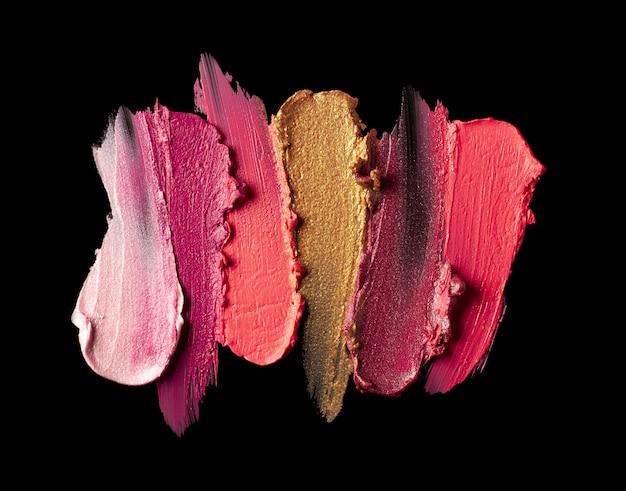 Multicolored lipstick sample smudge black isolated background