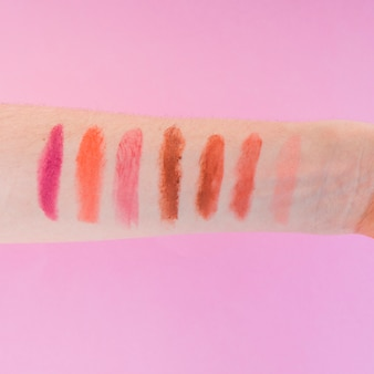 Multicolored lipstick shades on female's hand over pink background