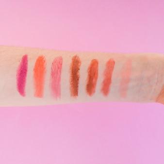 분홍색 배경 위에 여성의 손에 여러 가지 빛깔의 립스틱 음영