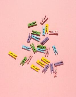 Разноцветные маленькие деревянные прищепки для одежды на розовом фоне. вид сверху.