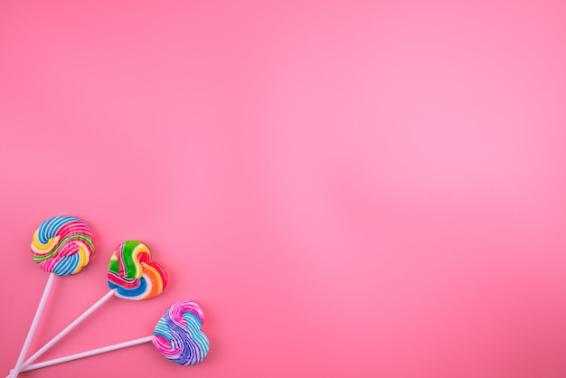 Multicolored lollipops on a pink background