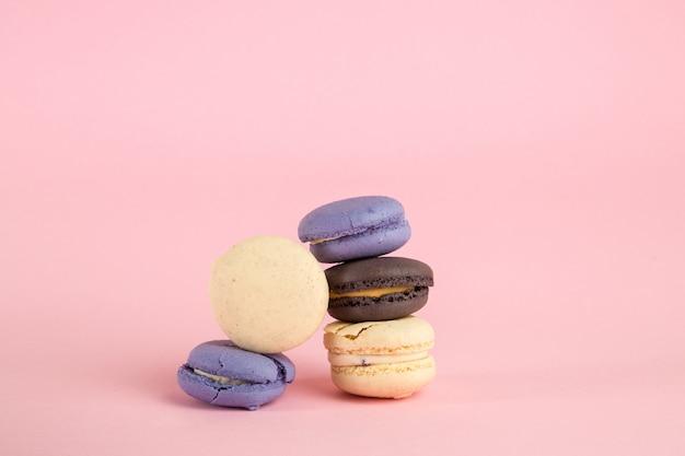 ピンクの孤立した背景に色とりどりのマカロニクッキー