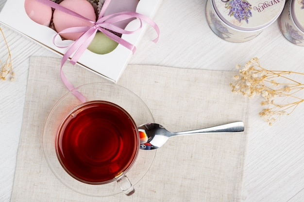 色とりどりのマカロンと軽い木製のテーブルの上のお茶モーニングティーとお菓子上面図