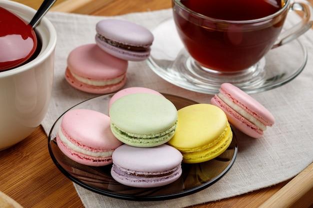 色とりどりのマカロンと木製トレイのお茶モーニングティーとお菓子