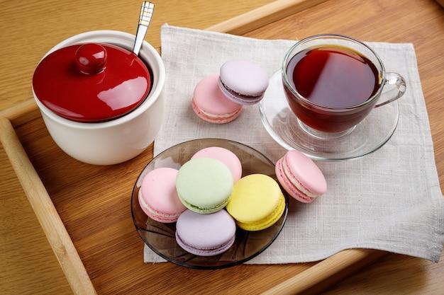 여러 가지 빛깔의 마카롱과 나무 쟁반에 차 한 잔 아침 차와 과자